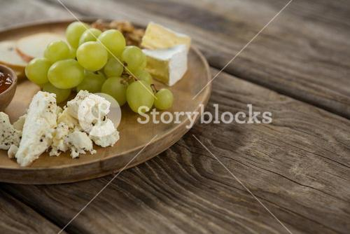 Cheese and grapes on wooden plate
