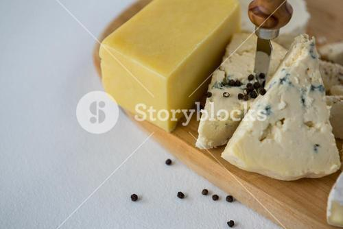 Variety of cheese with black pepper and knife on wooden board