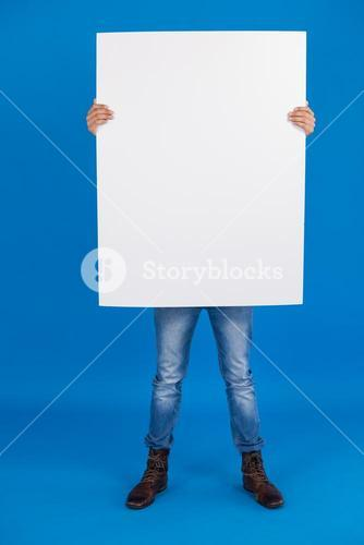 Man holding a blank placard in front of his face
