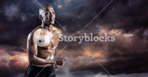 Athlete running against dark cloudy background