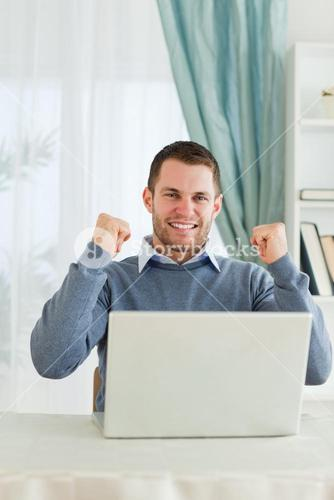 Businessman celebrating achievement in his homeoffice