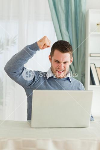 Businessman with raised fist in his homeoffice