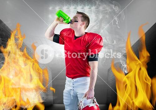 Player drinking energy drink in stadium against fire in background