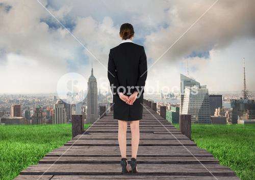 Businesswoman standing with hands on hip on wooden walkway