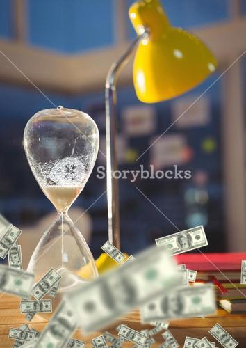Close up of lamp and hourglass with money on desk