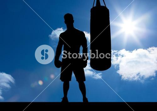 Silhouette of boxer with punching bag against sky background