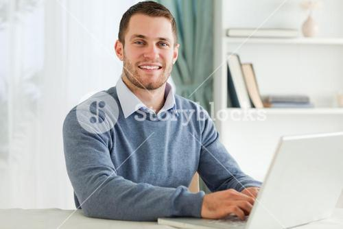 Smiling businessman with laptop in his homeoffice