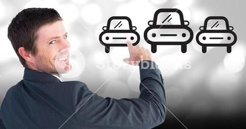 Businessman pointing at car icons against bokeh background