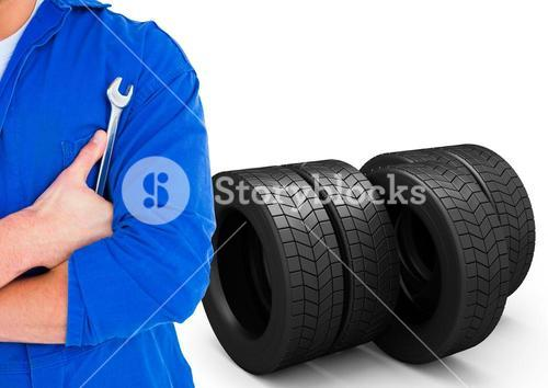 Mid section of mechanic holding a wrench against tires in background