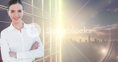 Businesswoman standing with arms crossed against skyscraper in background