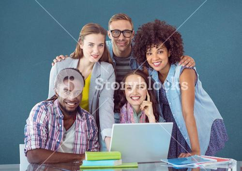 Happy classmates using laptop on table