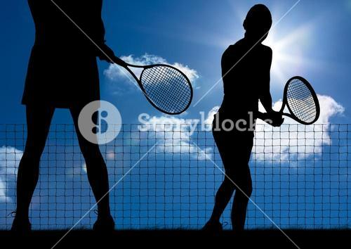 Silhouette of tennis player with rackets against sky background