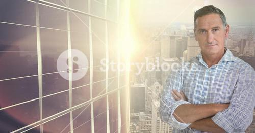 Businessman standing with arms crossed against cityscape in background