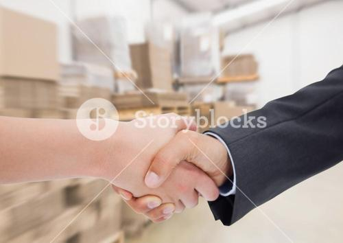 Business executives shaking hands against warehouse in background