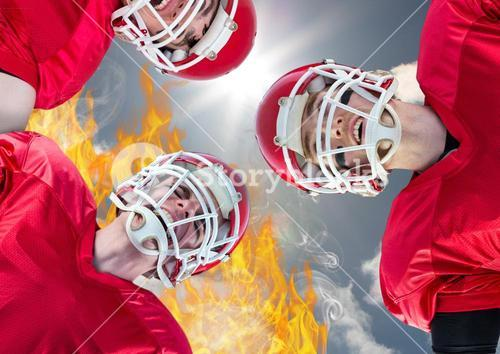 Aggressive players with helmets against fire and sky in background