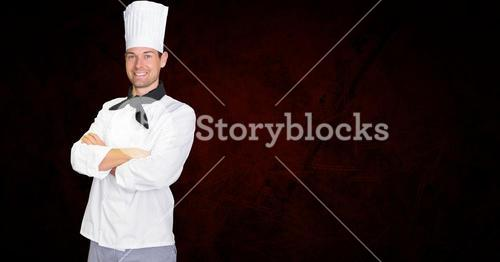 Confident chef standing with arms crossed against black background