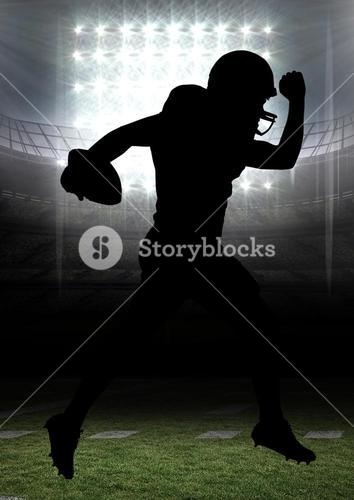 Silhouette of american football player running with a ball in stadium