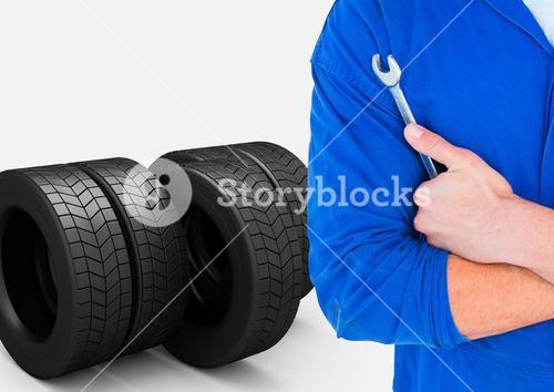 Mechanic holding wrench with tyres in background