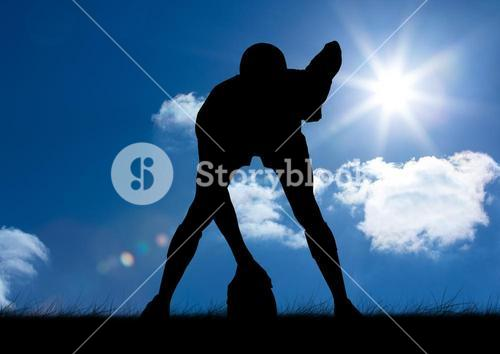 Silhouette athlete standing with rugby ball on a sunny day