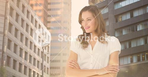 Female executive standing with arms crossed against city background