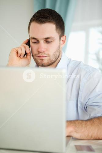 Businessman in his homeoffice using his cellphone