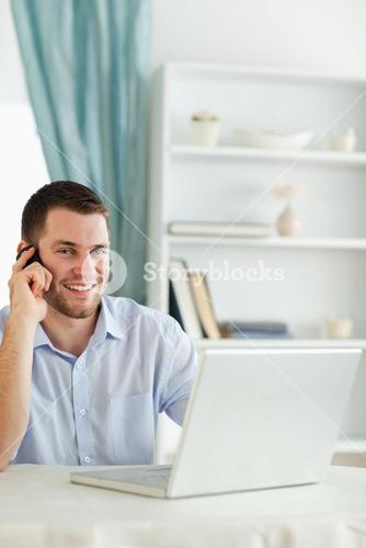 Smiling businessman in his homeoffice on the phone