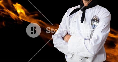Male chef holding skimmer and standing with flame in background