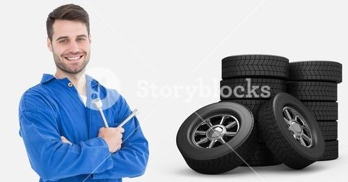 Smiling mechanic holding lug wrench and standing next to tyres