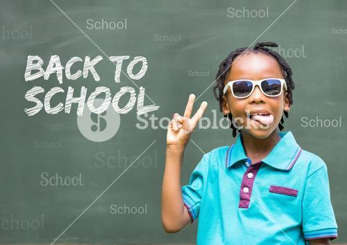 Schoolboy wearing sunglasses and gesturing with back to school text on chalkboard
