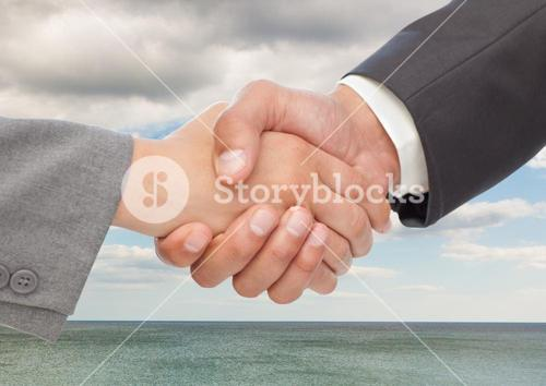 Businesspeople shaking hands against sea and clouds