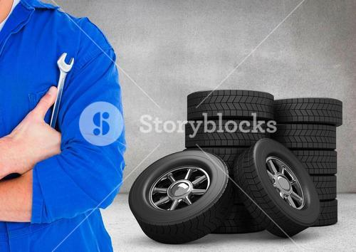 Mechanic holding lug wrench with tyres in background