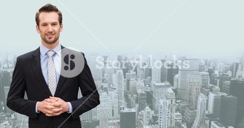Businessman standing with hands clasped against cityscape