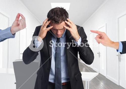 Frustrated businessman standing with hands on forehead