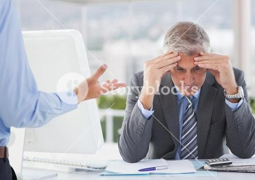 Frustrated businessman sitting with hands on forehead
