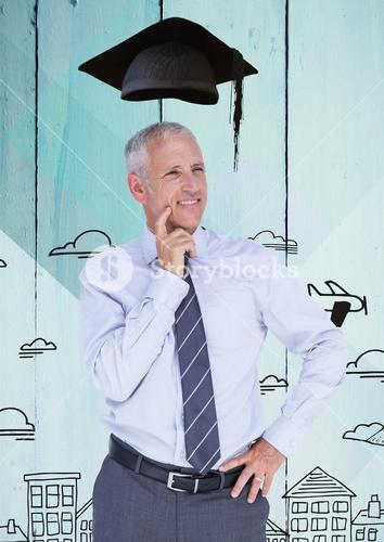 Smiling male executive standing with mortarboard above head