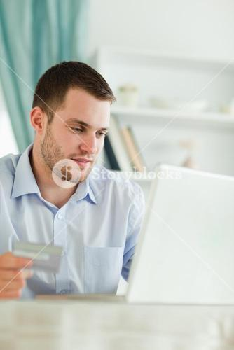 Businessman with credit card and laptop in his homeoffice