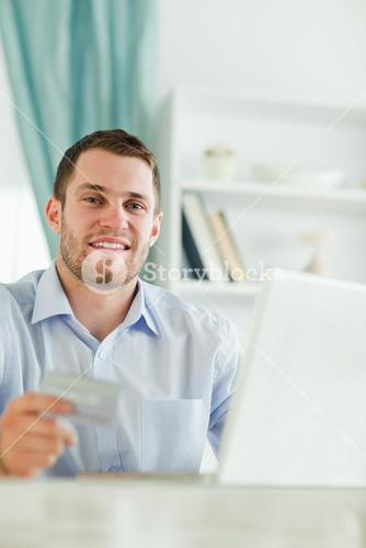 Businessman with credit card and notebook in his homeoffice