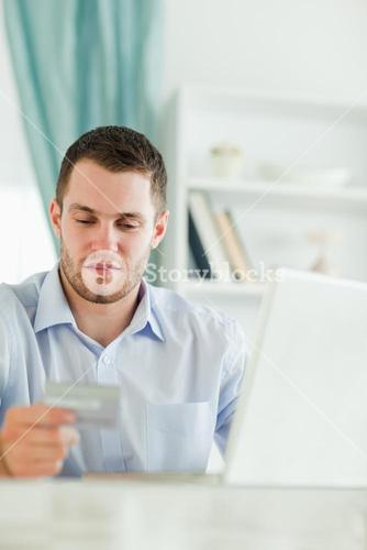 Businessman with laptop and credit card in his homeoffice