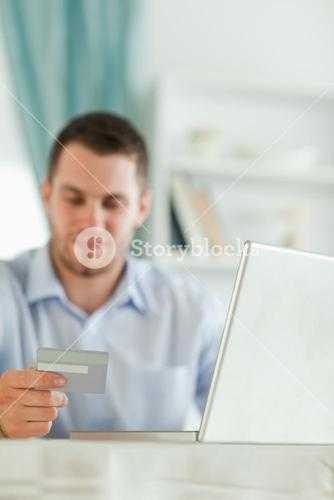 Businessman with notebook and credit card in his homeoffice