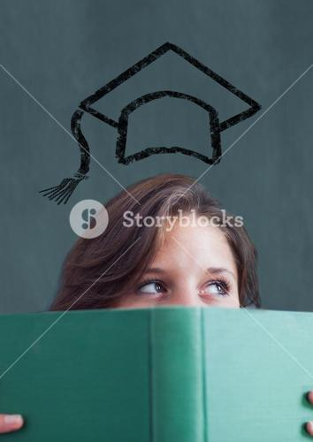 Teenage girl holding book with mortarboard above head