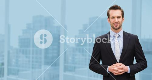 Businessman standing with hands clasped