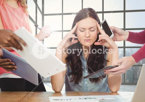 Stressed woman sitting with hands on forehead