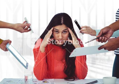 Stresssed woman sitting with hands on forehead