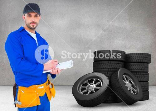 Serviceman writing on clipboard and standing next to tyres