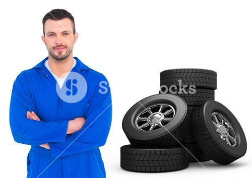 Car mechanic standing with arms crossed and tyres on white background
