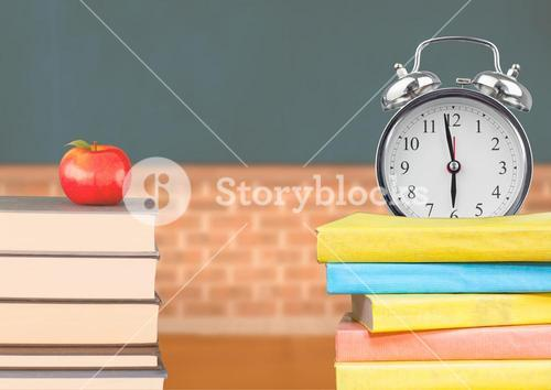 Apple and alarm clock on pile of books