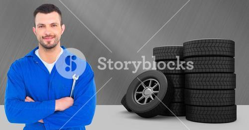Car mechanic standing with arms crossed and tyres on grey background