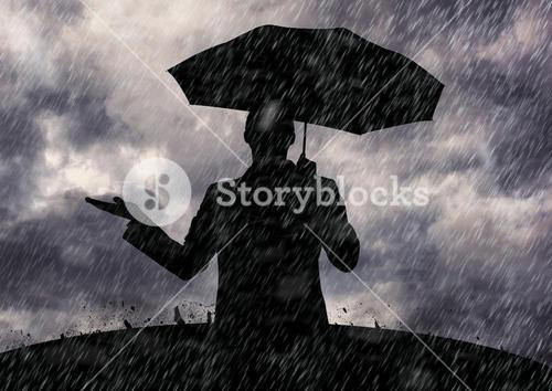 Silhouette of man holding umbrella standing in the rain
