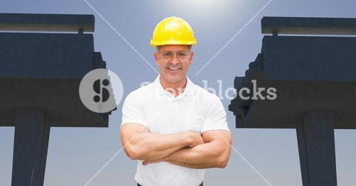 Architect in hardhat and arms crossed with broken bridge in background