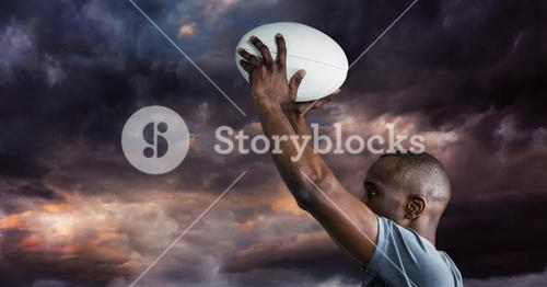 Man holding rugby ball against cloudy sky